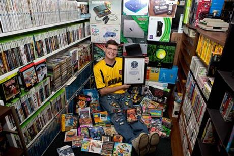 Thomasson poses in his basement with the record certificate and huge collection of games (AP Photo/Brianna Blank)